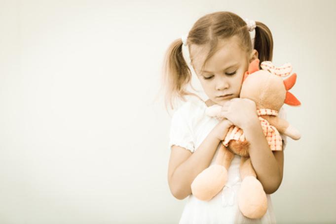 Kleinnes Mädchen hält Plüschtier feste an sich